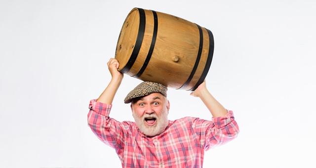 Homem de barba branca carregando barril de cerveja.
